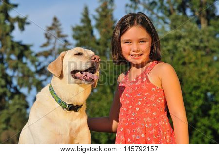 Portrait of adorable little girl with her labrador dog outside