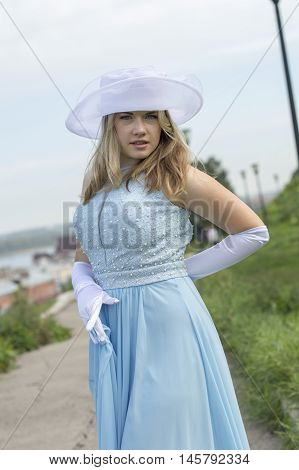 A young girl in a blue dress with white hat.
