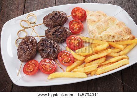 Kofta kebab, turkish minced meat skewer with pita bread and french fries