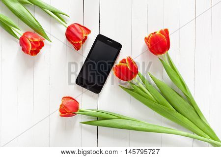 Spring bouquet of red tulips and black mobile phone on a white wooden background with copy space. View from the top with space for signature.