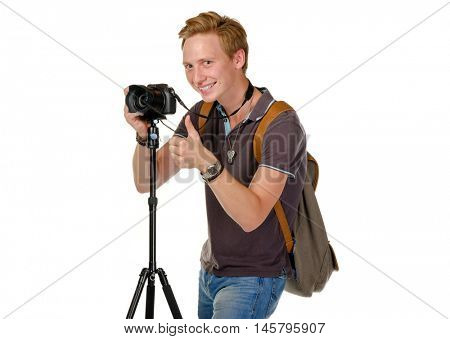 Young man traveler taking pictures by dslr camera on tripod isolated on white. Thumb up