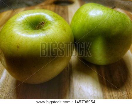 green apple closeup on a wooden cutting board.