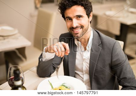 Handsome man eating at the restaurant