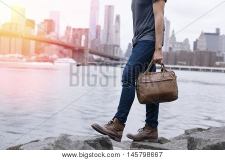 Closeup of a young entrepreneur going for a walk, wearing boots and a briefcase in New York