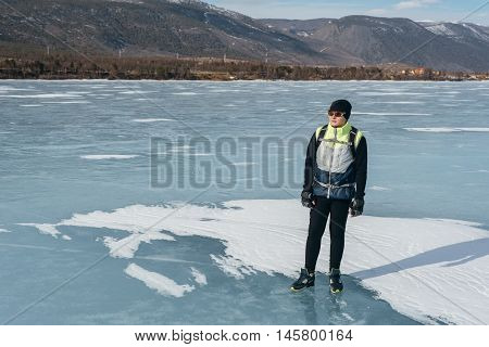 Traveler standing on the ice of Lake Baikal. Equipment for the cycling part for cold weather. On his back hangs a bicycle backpack sports gloves on his hands.