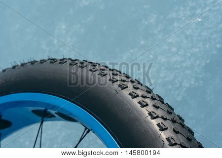 Fatbike (also called fat bike or fat-tire bike) - Cycling on large wheels. The wheel is on ice close-up shot.