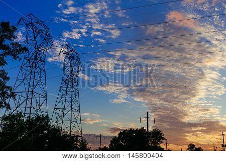 High Voltage Power Pylons In Sunset Scene Twilight