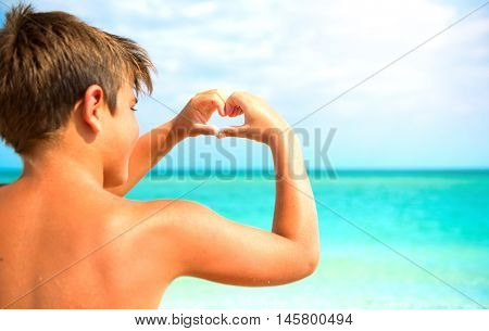 Happy little boy making heart with his hands over Ocean or Sea background. Joyful kid showing heart from Hands with Seascape inside. Tropical Resort. Vacation concept. Summer holidays. Tourism