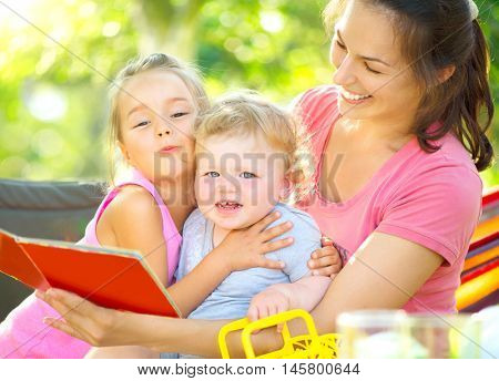Happy mother reading book to her little babies in sunny park. Joyful young family with children. Mom and kids having fun outdoors in orchard garden, playing together. Laughing, hugging, enjoy nature