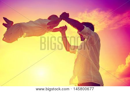 Father with his little son playing together, dad and child having fun outdoors. Joyful Family. Free, freedom concept. Summer Holidays, vacation