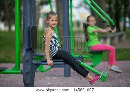 Cute little girls is engaged in sports equipment outdoor.