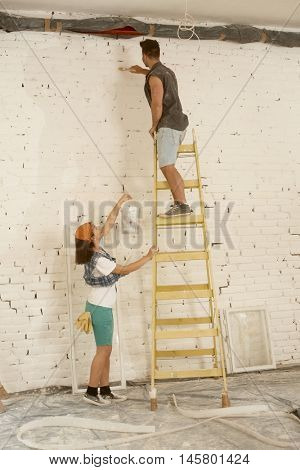 Young couple renovating home, man painting wall on ladder, woman passing painting.
