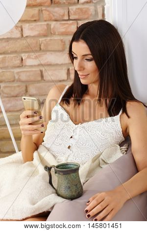Young woman using mobilephone, sitting at home, drinking tea.