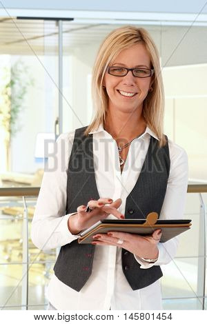 Happy blond businesswoman using tablet, looking at camera, smiling.