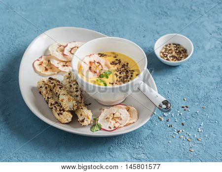 Pumpkin cream soup with apple chips and flax seed in a white bowl on a blue background. Healthy vegetarian food