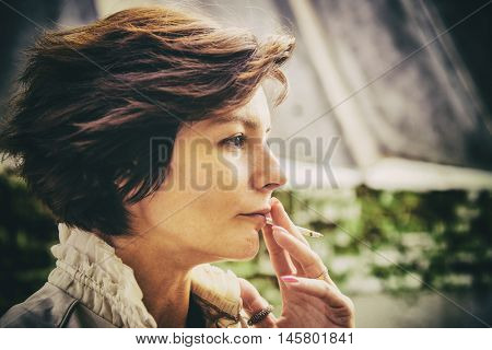 Young woman smokes on the street