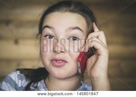Little teen girl calling by phone.