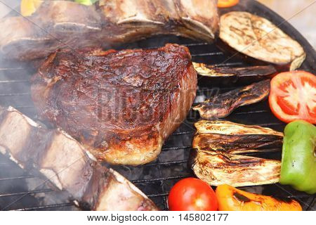 ready grilled beef meat fillet and asado ribs on bbq with garnish of tomatoes sweet bell pepper and eggplants