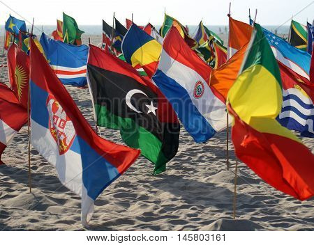 International flags in colorful group swaying in the wind on sandy beach.