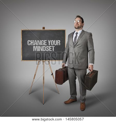 Change your mindset text on  blackboard with businessman carrying suitcases