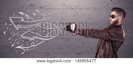 A hipster guy opening his point of view through looking a vintage camera concept with illustratied drawn arrows on urban wall