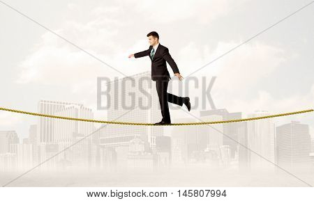 A young elegant businessman walking on tight golden rope in front of city buildings landscape background concept