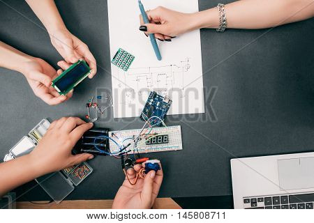 Teamwork engineering of electronic construction. Top view on workplace with hands working with wiring diagram and breadboard with cables and components, free space
