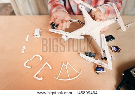 Electronics of disassembled drone repairing. Master connecting electronic elements to quadrocopter. Modern technologies, innovation, hobby, aeromodelling concept poster