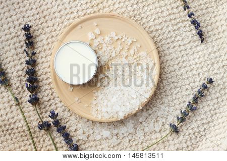 Natural skincare ingredients. Sea salt, dried lavender, facial moisturizer, beige towel.