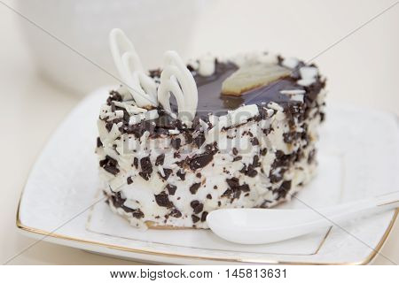 Delicious cake on plate on table on light background