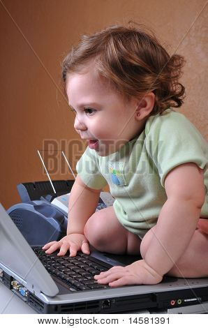 Baby sitting ON the laptop smiling at screen