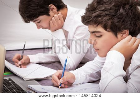 Two teenage boys doing homework at home, writing something in their notebooks, enjoying studies, education concept