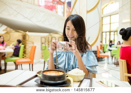 Woman taking photo on digital camera before having the meal
