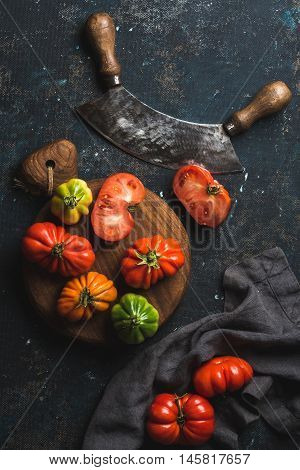 Fresh colorful ripe Fall heirloom tomatoes on wooden board, herb chopper knife for cooking or salad making over grunge dark plywood background, top view. Harvest vegetable cooking conception.