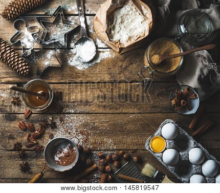 Christmas holiday cooking and baking ingredients. Cookie molds, spices, flour, eggs, cocoa powder, sugar, honey, nuts on old rustic wooden background. Top view, copy space