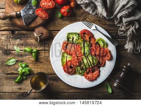 Heirloom tomato salad with olive oil, balsamic vinegar and basil over old rustic wooden background, top view, horizontal composition