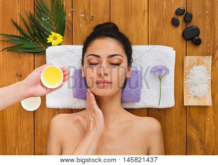 Portrait of woman patient in ayurveda spa wellness center lying on wood with aroma spa accessories. Young beautiful indian girl with ideal clean skin relax with closed eyes in beauty parlor.