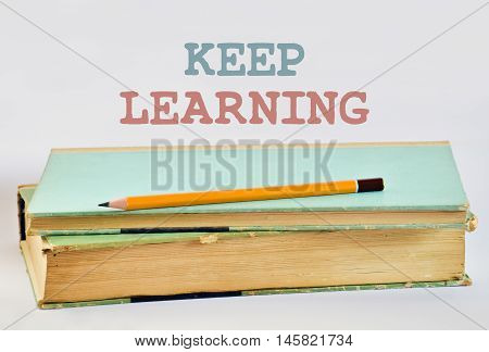 Two old books and text Keep Learning on bright background