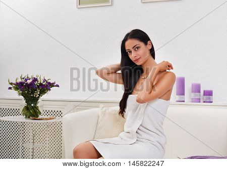 Portrait of woman patient in spa wellness center interior. Young beautiful indian girl, long-haired brunette, dressed in white towel in cosmetology cabinet or beauty parlor.