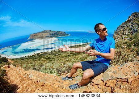 male traveler sitting on the trail against sea and blue sky at early morning. Balos beach at background. man gesture invites to pass