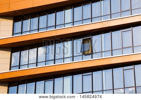 Modern office block with rows of continuous windows with one single window pushed open and the glass reflecting the sky and clouds view from below looking up