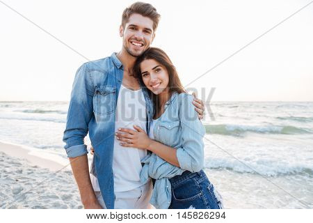 Smiling young couple in love hugging on the beach