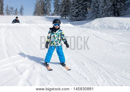 Cute Little Boy, Skiing Happily In Austrian Ski Resort In The Mountains