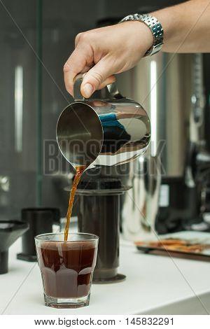 Barista pouring fresh coffee in a transparent glass. Coffee prepared in AeroPress. Subject of professional preparation of coffee, barista's secrets, invigorating fresh coffee, etc.