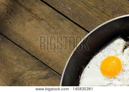 a dish of fried eggs in a hot pan on old wooden surface top view / sunny fried eggs on a griddle