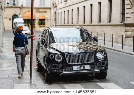 PARIS FRANCE - MAY 21 2016: Woman admiring the luxury Bentley Bentayga Hybrid SUV on the streets of Paris France