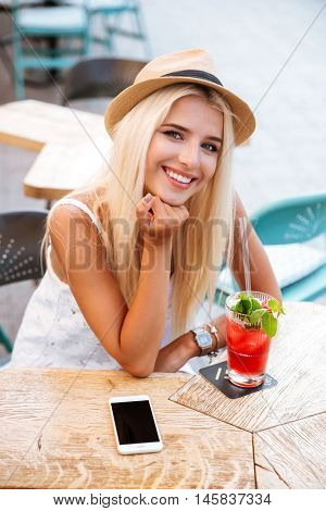 Happy pretty young woman with blank screen mobile phone drinking cocktail in outdoor cafe