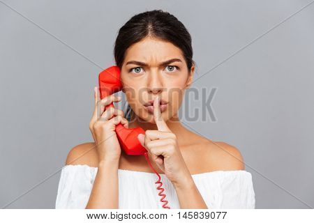 Beautiful young woman talking on the phone tube and showing silence gesture isolated on a gray background