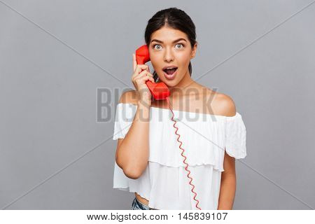 Amazed beautiful woman talking on the phone tube isolated on a gray background
