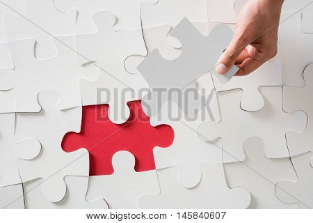 Hand holding jigsaw puzzle piece. Close up of businessman hand fixing jigsaw puzzle piece. High angle view of man finding business problem solution. Top view of hand completing white jigsaw puzzle.
